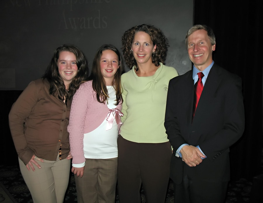 Crescentia Healy-True with her daughters and New Hampshire Gov. John Lynch as she receives Volunteer of the Year Award.